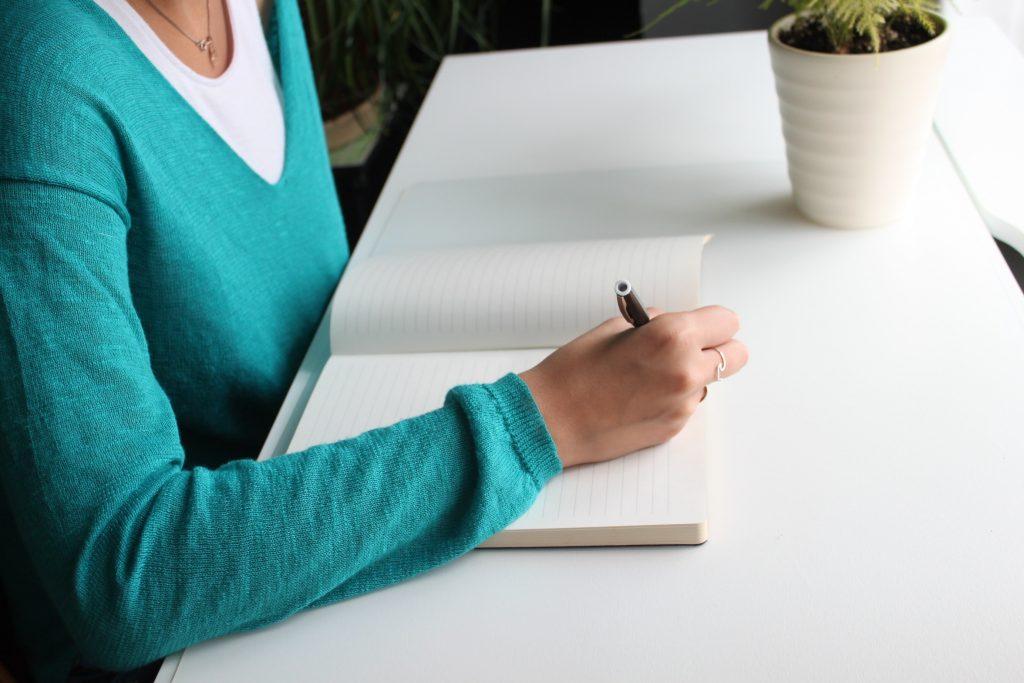 A imagem possui um elemento do sexo feminino, com uma esferográfica na mãe a escrever num caderno, dando a ideia que está a fazer copywritting.