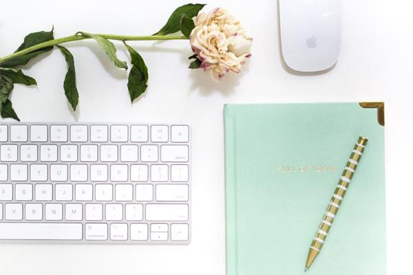 A imagem contem um teclado, um rato, um livro, uma caneta e uma flor, simbolizando o copywriting, que é um dos nossos serviços.