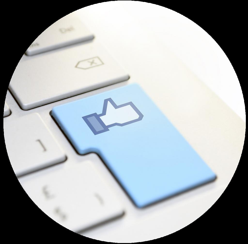 """Um teclado onde a tecla enter é azul e tem o """"like"""" do facebook, simbolizando todas as redes sociais."""