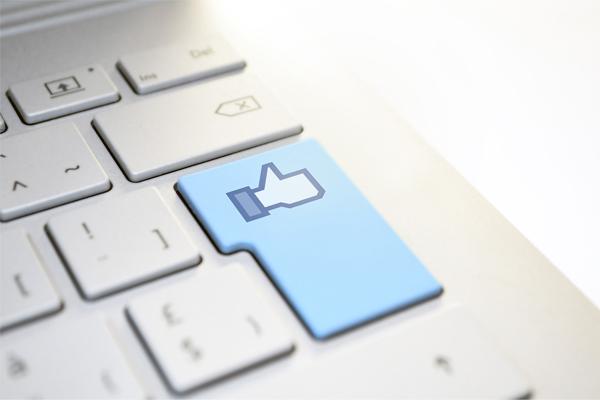 """Teclado com a tecla do enter em azul e a imagem do """"Gosto"""" do Facebook, porque gestão de redes sociais é um dos nossos serviços."""