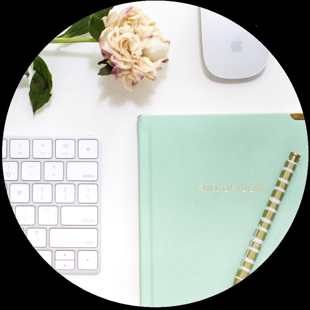 A imagem tem um teclado, um rato, um caderno, uma caneta e uma flor. Estes elementos remetem para o copywriting, em que a flor é a criatividade.